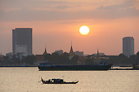 Phnom Penh, Cambodia. Sunset behind Royal Palace, seen from aboard a cruise to the confluence of Tonle Sap and Mekong river. Barges pumping up sand from the river ground for construction materials.