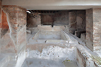 Three large tubs, interconnecting but without a drainage system, and five oval basins, where the workers washed the fabric by trampling on it, in the triclinium of the Fullonica di Stefanus, or Fullonica of Stephanus, a laundry in Pompeii, Italy. Pompeii is a Roman town which was destroyed and buried under 4-6 m of volcanic ash in the eruption of Mount Vesuvius in 79 AD. Buildings and artefacts were preserved in the ash and have been excavated and restored. Pompeii is listed as a UNESCO World Heritage Site. Picture by Manuel Cohen