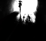 The silhouette of a figure carrying an umbrella along a rainy street