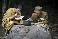 """Actors dressed as Chinese World War Two soldiers eat their lunch on the set of """"The Last Prince"""" television series on location near Hengdian World Studios near Hengdian July 24, 2015. Hundreds of well-trained actors and other professionals are available at the Hengdian World Studios. The well-organised team coordinate complicated battle scenes to satisfy the huge appetite for productions about the war against Japan. Director Li Xiaoqiang said the series is about a Qing Dynasty prince, who joined the Chinese nationalist army after suffering family misfortune. """"After he learnt more about the Communist Party, the prince began to understand what real revolution and the anti-Japanese war meant, and turned to the Communist Party to fight Japan"""", the director added. According to local media, more than 10 new movies, 12 TV dramas, 20 documentaries and 183 war-themed stage performances will be released in China to coincide with the 70th anniversary of the end of World War Two. REUTERS/Damir SagoljPICTURE 16 OF 28 FOR WIDER IMAGE STORY """"BEHIND THE SCENES OF A CHINESE WAR DRAMA"""".SEARCH """"SAGOLJ STUDIO"""" FOR ALL PICTURES."""