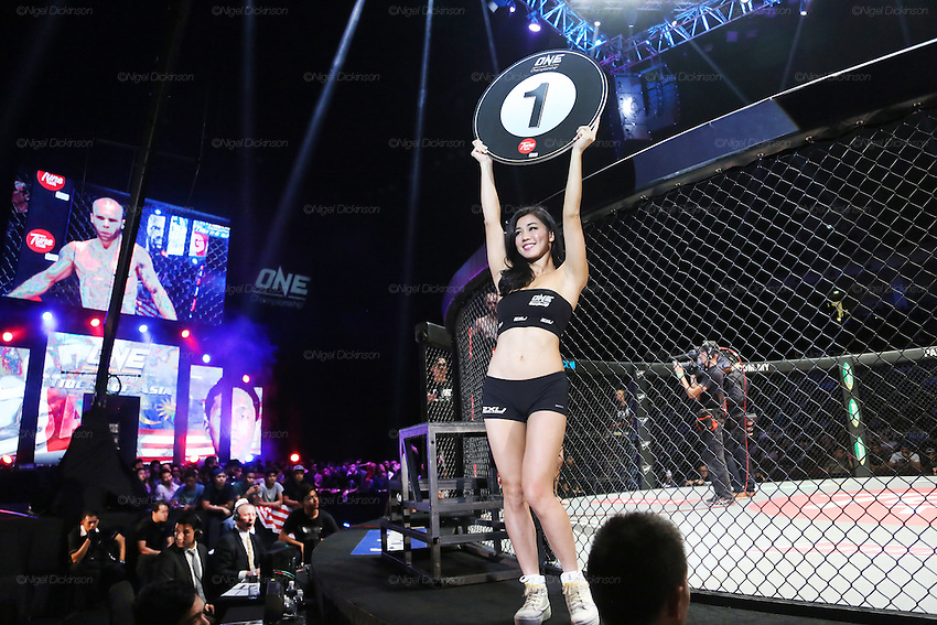 Ring girl walks around the cage announcing first round<br />