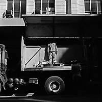 A Coca Cola delivery man stands on his delivery truck's trailer, his head obscured by heavy shadow.