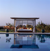 A charming curtained pavilion furnished with a comfortable sofa and cushions is situated at the edge of the pool