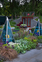 Roof deck, house, Glass obelisks with solar power panels for night lighting in garden in spring with irises, ornamental grass, allium, Lavandula stoechas, ornamental grass, modern privacy fence, gabions, Salvia sage herbs, seats, container garden agacve, trees, stone patio and wood deck and bench