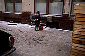 Moscow, Russia<br /> Soviet Union<br /> December 10, 1991<br /> <br /> A young child, all dressed up for winter's cold, waits on the street.<br /> <br /> In December 1991, food shortages in central Russia had prompted food rationing in the Moscow area for the first time since World War II. Amid steady collapse, Soviet President Gorbachev and his government continued to oppose rapid market reforms like Yavlinsky's &quot;500 Days&quot; program. To break Gorbachev's opposition, Yeltsin decided to disband the USSR in accordance with the Treaty of the Union of 1922 and thereby remove Gorbachev and the Soviet government from power. The step was also enthusiastically supported by the governments of Ukraine and Belarus, which were parties of the Treaty of 1922 along with Russia.<br /> <br /> On December 21, 1991, representatives of all member republics except Georgia signed the Alma-Ata Protocol, in which they confirmed the dissolution of the Union. That same day, all former-Soviet republics agreed to join the CIS, with the exception of the three Baltic States.