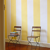 A pile of colourful napkins sits on one of a pair of chairs against a yellow and white striped wall