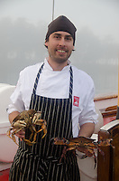 Chef James Maine shows off fresh caught red rock crabs (Cancer productus) aboard SV Maple Leaf, Gulf Islands, British Columbia, Canada