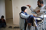 Hudda Mohammed, 40, who is paralysed from the waist down after a cluster bomb exploded next to him while he was clearing a field. He is seen here being cared for by his wife, Imam Sa'ad, 27.