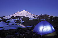 Tent glowing below Mt Baker on a clear evening, North Cascades, Cascade Mountains, Washington