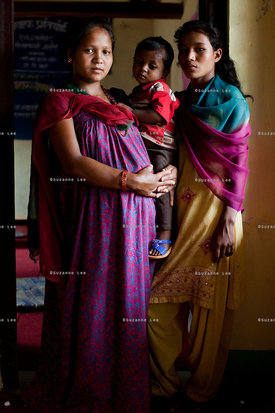 Manisha Sunar (left), 18, carries her 2 year old son, as her husband's niece Pramila Bhujel, 13, stands next to her at the information center near their home in Lekhapharsa vilage, Surkhet district, Western Nepal, on 30th June 2012. Manisha was married off when she was 14 but secretly used contraceptives with the help of her husband's sister. When he found out, he forced her to stop and she was soon pregnant with no money to terminate it. She's now 8 months pregnant again even though her husband neglects and abuses her and her son. He also mistreats Pramila and earlier this year, a fellow villager secretly married Pramila off to a man in his mid-20s but the marriage was annulled the day after when her uncle, Manisha's husband found out and wrestled her back. Now, Pramila is still mistreated by her uncle and is considered a divorcee since she spent one night with the man she was married to, but she is back in school and has ambitions to become a nurse. In Surkhet, StC partners with Safer Society, a local NGO which advocates for child rights and against child marriage. Photo by Suzanne Lee for Save The Children UK