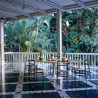 This large porch overlooking the lush garden displays an impressive stone and marble floor and is furnished with a Saarinen table