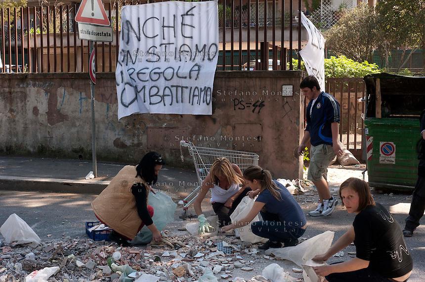 Roma  10 maggio 2011.Cassonetti rovesciati bloccano via Valle dei Fontanili   al quartiere Torrevecchia, dove è in corso la protesta  degli  inquilini dell'ex-residence Bastogi dopo l'arrivo di una pattuglia di vigili urbani per sgomberare un appartamento. Gli inquilini ripuliscono la strada