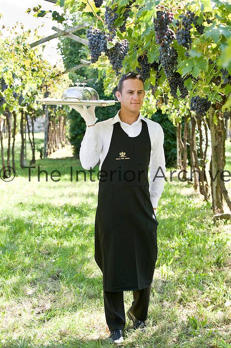 A waiter from the Ristorante Arquade near Verona carrying a silver tray through the vineyards where an al fresco lunch is taking place