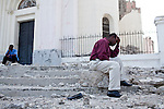 Men pray on top of the rubble of the destroyed national cathedral during a church service on July 11, 2010 in Port-au-Prince, Haiti.