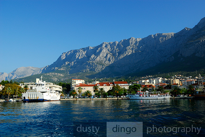 View from sea of town of Makarska and harbour, with Biokovo National Park, part of the Dinaric Alps, in background. Makarska, Croatia