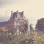 The Louvre, Paris, standing in the midst of the beautiful Tuileries gardens surrounded by flowers in bloom & statues