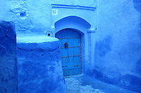 Studded wooden door, entrance to a house in a narrow street entirely painted blue in the medina or old town of Chefchaouen in the Rif mountains of North West Morocco. Chefchaouen was founded in 1471 by Moulay Ali Ben Moussa Ben Rashid El Alami to house the muslims expelled from Andalusia. It is famous for its blue painted houses, originated by the Jewish community, and is listed by UNESCO under the Intangible Cultural Heritage of Humanity. Picture by Manuel Cohen