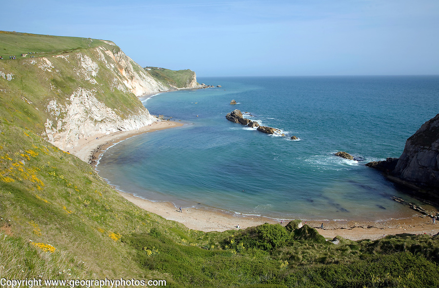 A line of limestone stumps cross Man o' War bay on the Jurassic coast near Lulworth Cove, Dorset, England