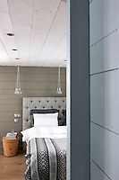 A buttoned linen headboard is complemented by a grey striped bed cover in the contemporary master bedroom