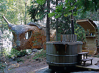 A wood encased hot tub on a deck overlooking this unusual cedarwood-clad house - known as the 'accordion' cabin, it is shaped like a turtle and has a retractable head
