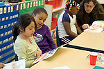 Oakland CA 1st-2nd grade students reading together in class