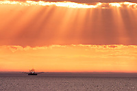 Sunray's shine down on a working fishing trawler off the coast of North Carolina on the Outer Banks.