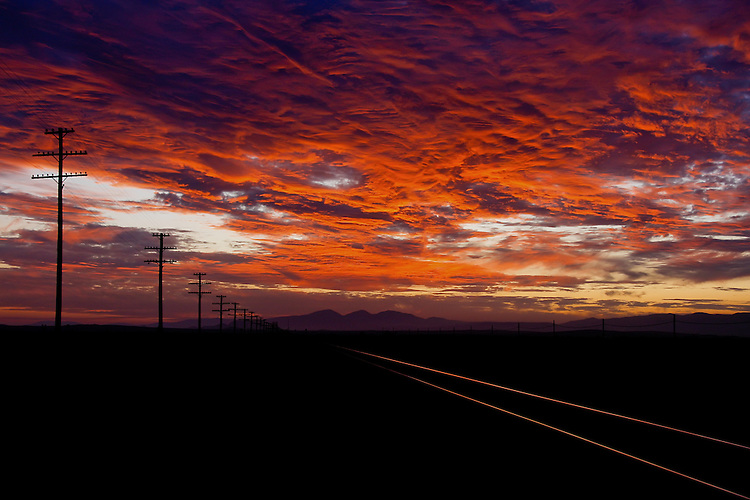 Train tracks trail off into the sunset as the sky catches fire. (Photo by Jeff Speer © www.JeffSpeer.com)