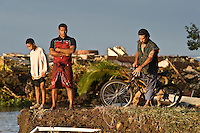 Young men from Poutasi village survey the damage 24 hours after the tsunami. More than 170 people died when a tsunami triggered by an 8.3 magnitude earthquake hit Samoa and neighbouring Pacific islands on 29/09/2009. Samoa (formerly known as Western Samoa)..