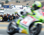 Fans watch Pramac Racing Team pilot Toni Elias of Spain at turn 11 during the MotoGP warm up practice, Sunday, July 29, 2012.