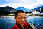 A young Buddhist monk seen against the Pho Chhu river next to the Punakha dzong (fortress) in Punakha, Bhutan. Phunakha was the capital of Bhutan and the seat of government until 1955, when the capital was moved to Thimphu. Punakha is the administrative centre of Punakha dzongkhag, one of the 20 districts of Bhutan. Photo: Sanjit Das/Panos