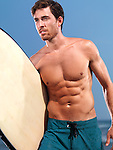 Muscular man with a surfboard at the sea enjoying summer sport activities