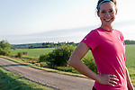 Young woman runner smiling at the camera a country road behind her. Manitoba farm land in the morning.