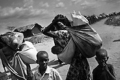 Somali women refugees are seen carrying ration and other supplies outside the Dagahaley refugee camp in the Dadaab refugee camp in northeastern Kenya. Hundreds of thousands of refugees are fleeing lands in Somalia due to severe drought and arriving in what has become the world's largest refugee camp. Photo: Sanjit Das/Panos