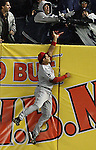 The Angels' Bobby Abreu jumps up to try to catch Alex Rodriguez' home run in the 11th inning during game two of the American League Championship Series at Yankee Stadium on Saturday, Oct. 17, 2009, but Yankees fans prevent him from reaching the ball.