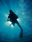 Kenting, Taiwan -- Diver against the rays of a sunburst.