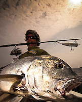 This closer shot shows how big the fish is and how massive is its head. The fisherman is holding the rod with his teeth and the lure, a large popper, is clearly visible in the image