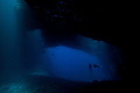 Looking out from the back of Blue Holes into the deep blue open sea. The shafts of light are from the holes in the top of the cavern that give Blue Holes its name, Palau Micronesia. (Photo by Matt Considine - Images of Asia Collection)