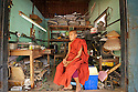 Novice monk (samanera) waits in a repair shop where old electric and electronic devices are piled.