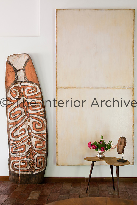 An Amat shield is placed next to a contemporary artwork by Ford Beckman, and a 'Metoko' Congo mask on the side table