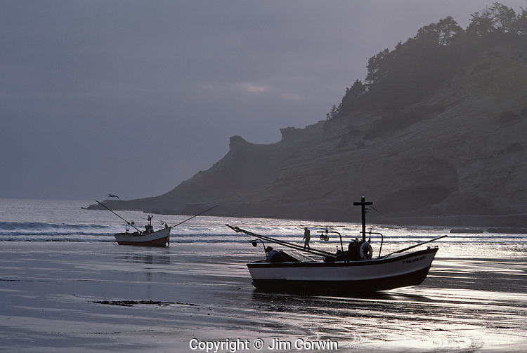 Dories along shoreline with storm clouds getting ready to launch at sunrise for fishing Cape Kiwanda State Park National Recreation Area near Pacific City northern Oregon coast Oregon State USA
