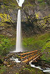 Scenic Elowah Falls with the wooden footbridge over the river from the Columbia River Gorge Scenic Area of Oregon. A rather large and beautiful waterfall, it is nearly 300 feet tall.
