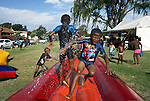 SOWETO, SOUTH AFRICA DECEMBER 10: Children play on a jumping castle during a birthday celebration on December 10, 2006 in Thokoza park in Soweto, Johannesburg, South Africa. Most birthdays for children have these jumping castles where the children play, and it usually takes up the whole garden. Soweto is South Africa?s largest township and it was founded about one hundred years to make housing available for black people south west of downtown Johannesburg. The estimated population is between 2-3 million. Many key events during the Apartheid struggle unfolded here, and the most known is the student uprisings in June 1976, where thousands of students took to the streets to protest after being forced to study the Afrikaans language at school. Soweto today is a mix of old housing and newly constructed townhouses. A new hungry black middle-class is growing steadily. Many residents work in Johannesburg, but the last years many shopping malls have been built, and people are starting to spend their money in Soweto. .(Photo by Per-Anders Pettersson/Getty Images)..