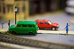 Hicksville, New York, USA. February 22, 2015. An unusual, thought-provoking scene is created with miniature model of a woman with her arm positioned around nobody, and minivan and SUV parked next to train tracks, at Model Train Exhibit hosted by Trainville Hobby Depot at the Broadway Mall. Donations were accepted at exhibit to support the Nassau County Empire State Games for the Physically Challenged.