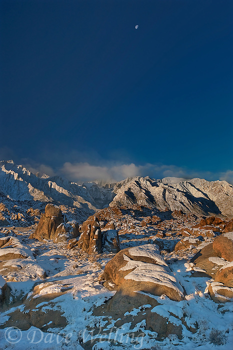 711700252 a clearing winter storm at sunrise partially shrouds lone pine peak mount whitney and mount russell in clouds with snow covered granite boulders of the alabama hills in the foreground in the eastern sierrras near lone pine california