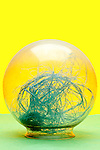 clear glass bowl with blue string object on yellow green background