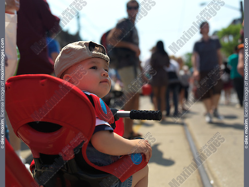 One year old baby boy on a tricycle at the middle of the street surrounded by people