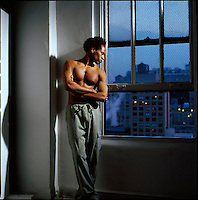 Shirtless African American man standing with nighttime city windows as background