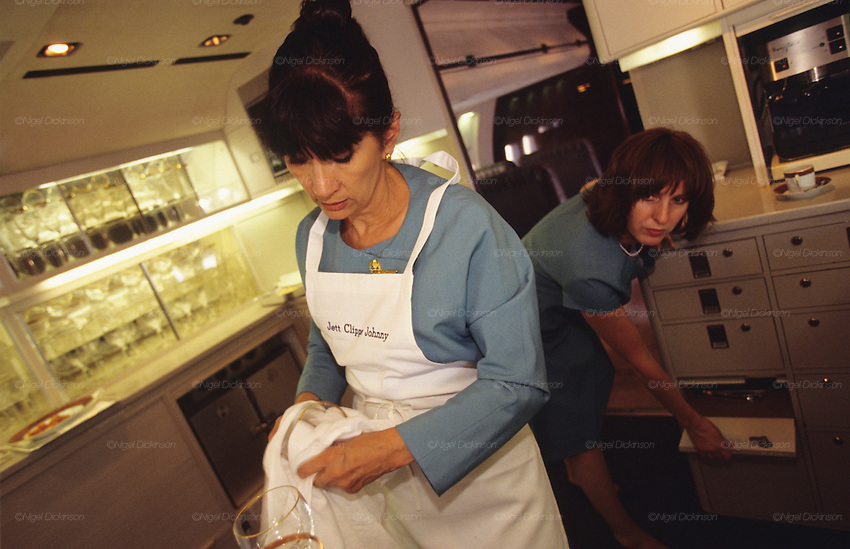 """Crew of John Travolta's jumbo jet. Stewards and stewardesses preparing food for guests..John Travolta is pilot of his very own jumbo jet, a 1964 Boeing 707-100 series. In 2003, John Travolta flew his jumbo jet around the world, in partnership with Quantas, to rekindle confidence in commercial aviation, and to remind us that elegance and style are a part of flying. The crew are dressed in tailor made authentic uniforms from the Quantas museum. The men's uniforms are styled on British Naval uniforms and the ladies' designed by Chanel. His jumbo jet sports a personalised number plate N707JT which speaks for itself. The aircraft is named """"Jett Clipper Ella"""" dedicated to his son and daughter. This jumbo together with his other aircraft are housed in purpose built hangars at his home in Florida, USA."""
