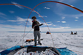 Scientists setting up tents for housing and equipment on a relatively flat spot on the Greenland ice sheet.