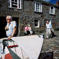 Elderly tourists eat ice cream outside an old cottage by the harbour in Mousehole, Cornwall.